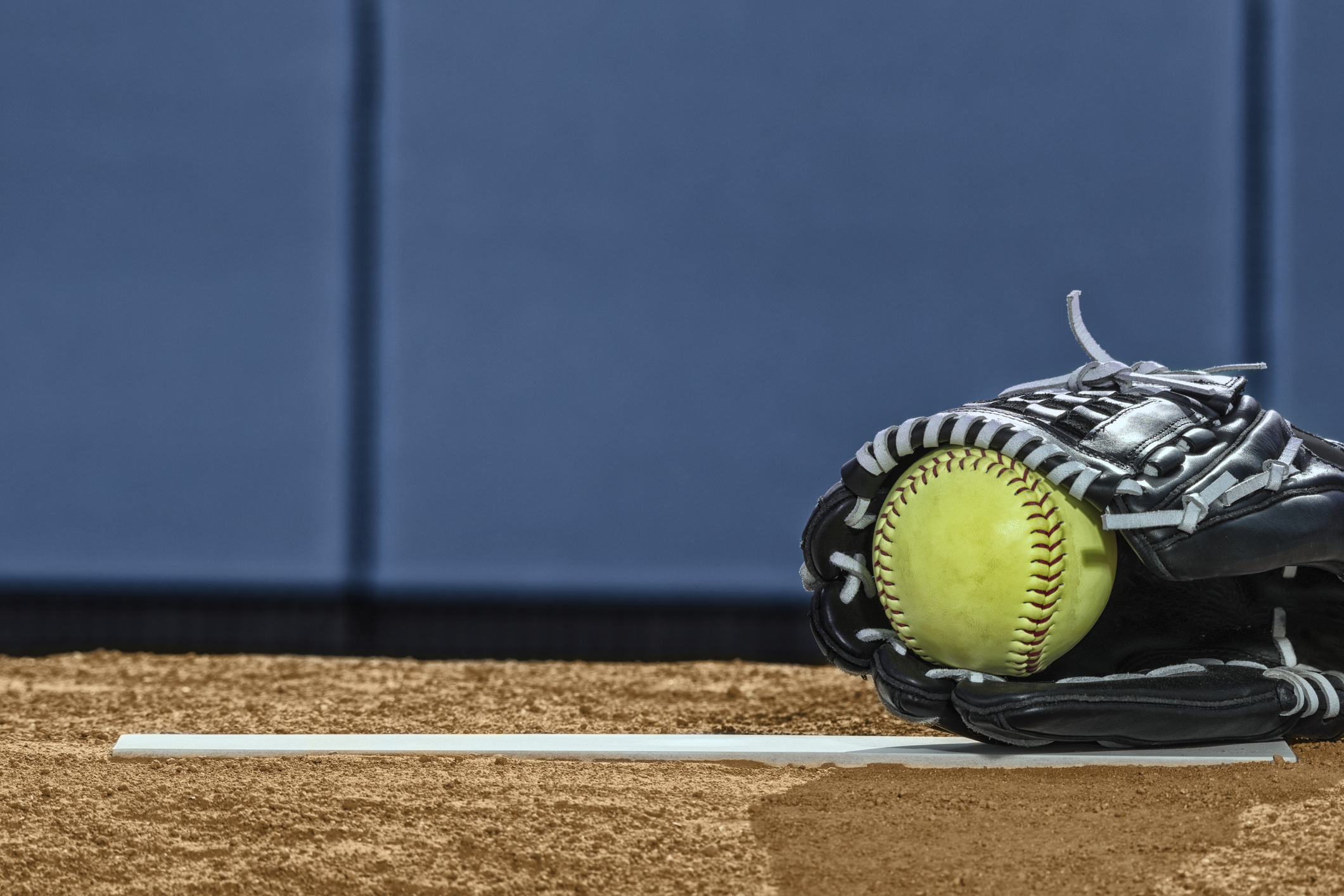 A low angle view of a new yellow softball in a black leather glove with white laces sitting of the rubber of a pitcher's mound with a blue padded wall in the background